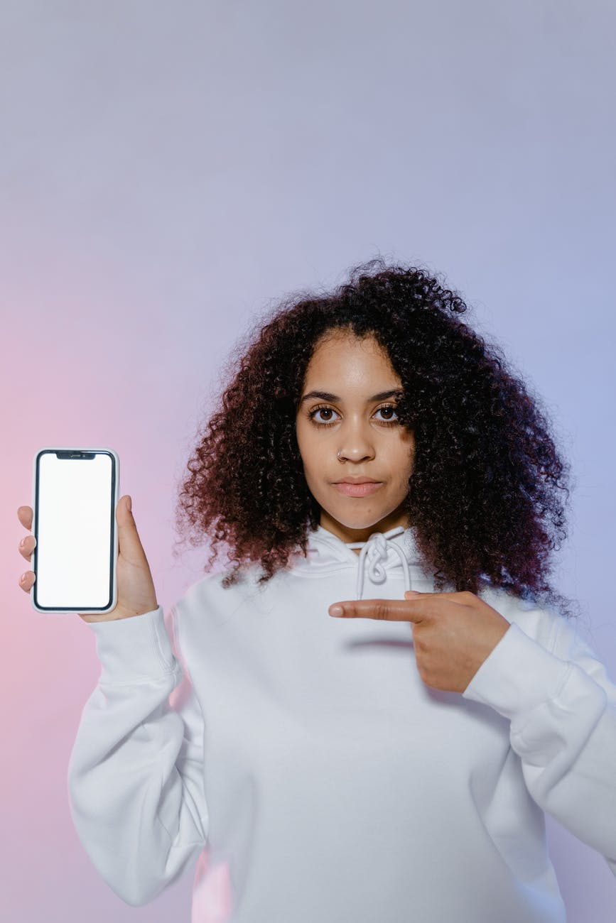 woman in white long sleeve shirt pointing at white mobile phone in her hand
